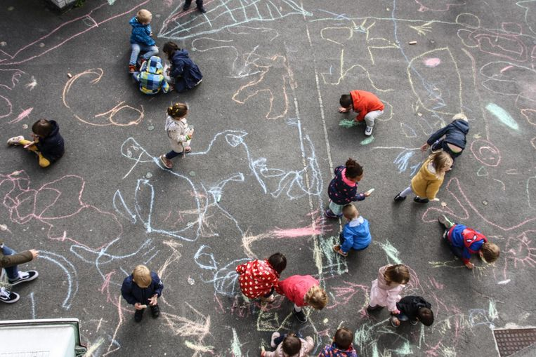 De kleuters van de Sint-Vincentiusschool in Buggenhout maken krijttekeningen op de speelplaats.
