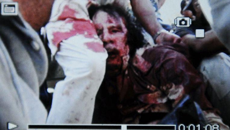 Een foto van de gsm van een strijder die kennelijk de zwaargewonde Muammar Kaddafi toont. Een NTC-functionaris bevestigt dat het inderdaad de ex-dictator is. © AFP Beeld