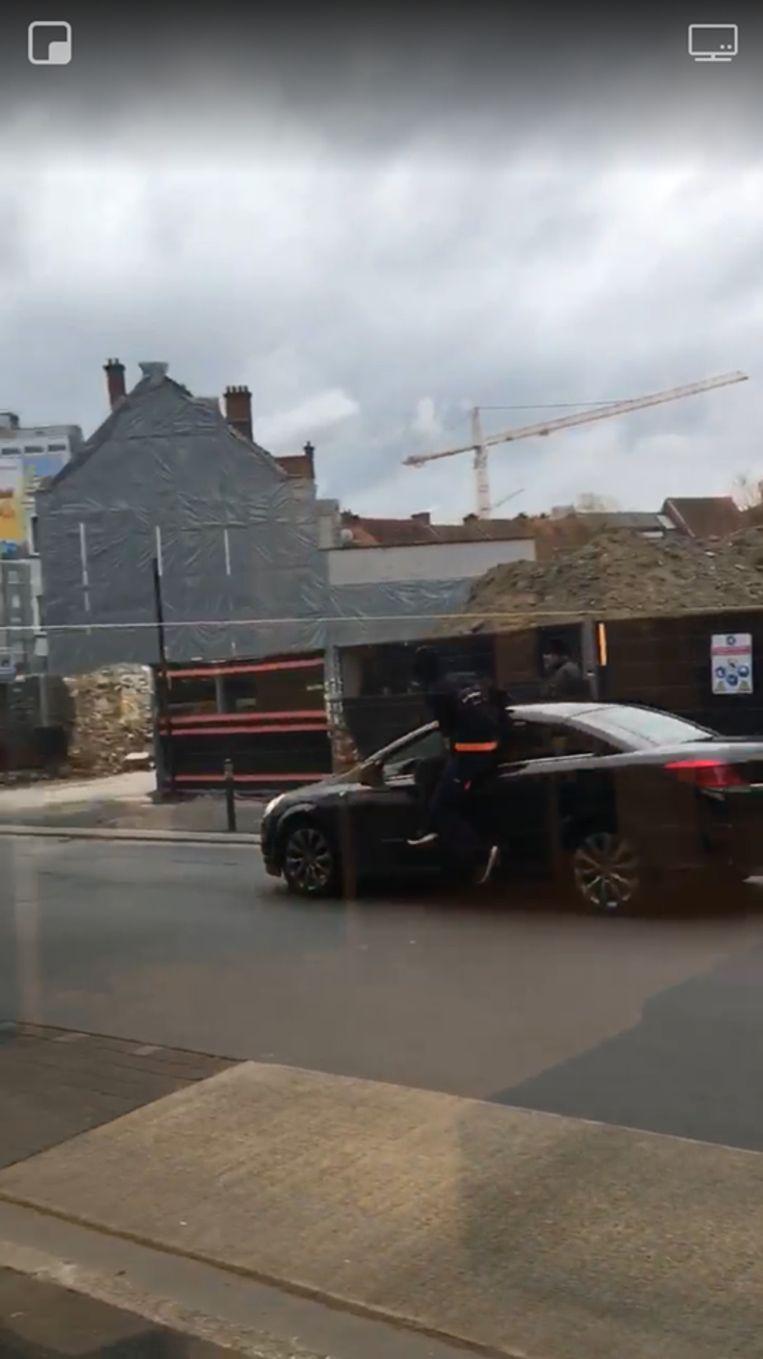 De man hangt aan het voertuig in Aalst.