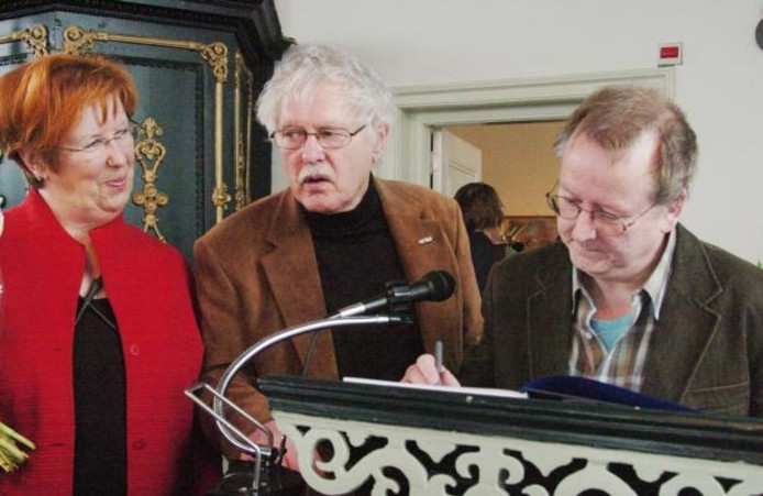 Aaldert Pol (midden) en Gerrit van Hezel signeren het eerste exemplaar van het Schoklandboek voor de voorzitter van Schuttevaer Annemarie Jorritsma.foto Hans Veenhuis