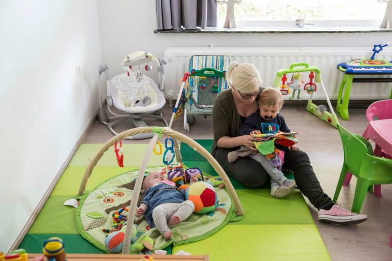 Een kinderverzorgster bekijkt samen met een peuter een boekje.