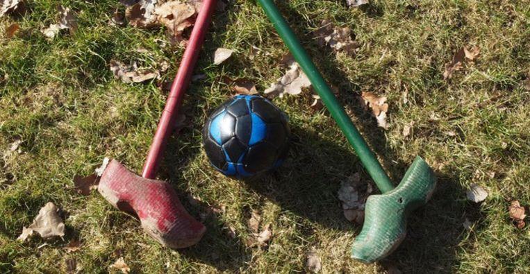 Bosgolf wordt gespeeld met sticks waar onderaan een boerenklomp aan vastgemaakt is.