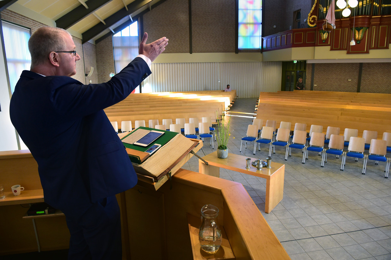 Dominee Arend-Jan de Boer van de Rehobothkerk  in Urk neemt zondagochtend de dienst op die de leden van de gereformeerde kerk even later thuis kunnen beluisteren.  Beeld Marcel van den Bergh / de Volkskrant