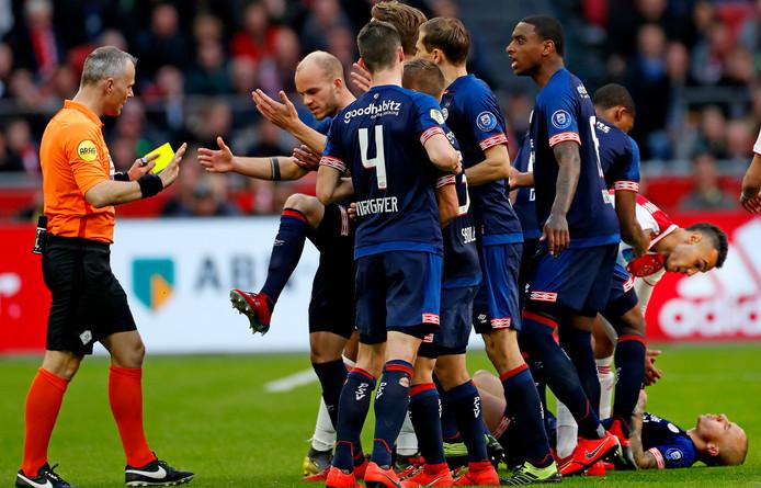 De PSV-ers, met voorop Jorrit Hendrix, protesteren bij scheidsrechter Kuipers tegen de gele kaart na de schop van Ajacied Mazraoui teren Angelino. Later zou de VAR ingrijpen en rood adviseren aan Kuipers.