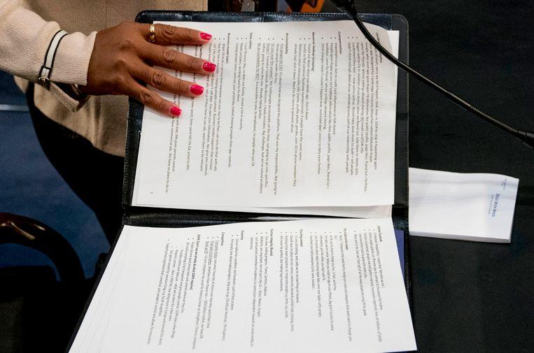 Een assistente van Zuckerberg sluit zijn map met aantekeningen tijdens een korte pauze.