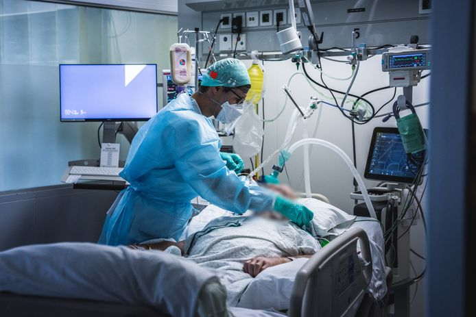 Een verpleegkundige helpt een patiënt op de afdeling intensieve zorg.