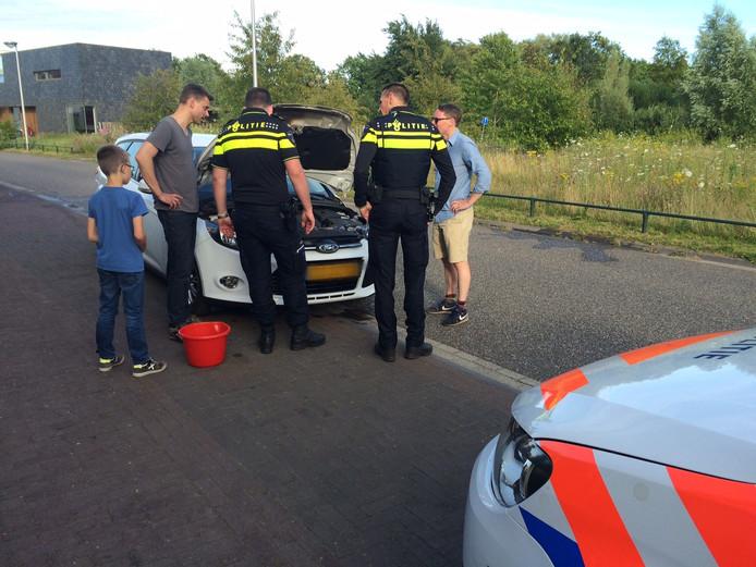 Politieagenten duwden met omstanders de auto naar de kant van de weg