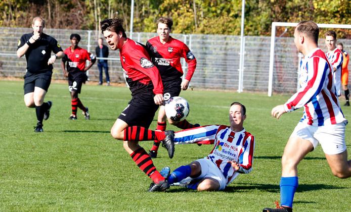 Oostburg (rood-zwart) blijft in de titelrace door een klinkende 5-1-zege op Hulsterloo.