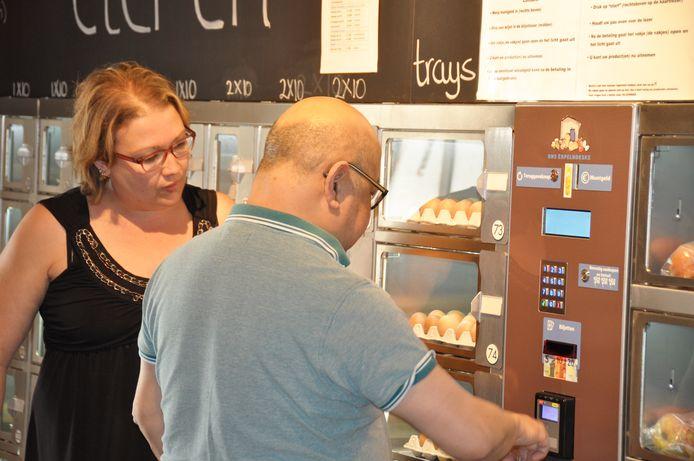 Mathilde Pruijsen helpt mensen op weg bij de nieuwe automaat met aardappelen, uien en appels. Rechts vaste klant Freek de Nijs uit Sprang-Capelle.