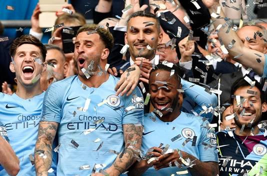 Khaldoon Al Mubarak gaat verscholen achter de feestende City-spelers na het winnen van de Engelse titel.