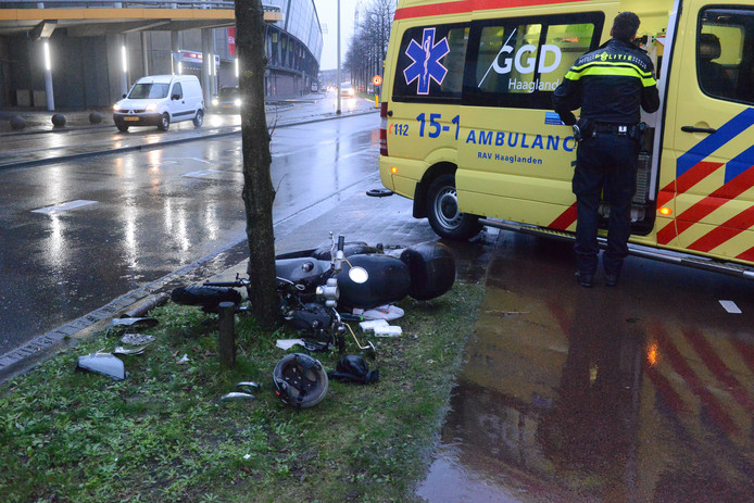 De scooter ligt in stukken na de botsing tegen een boom in de Waldorpstraat.