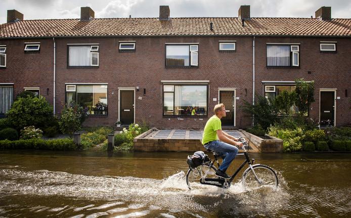 Een man fietst door een ondergelopen straat in Kockengen.