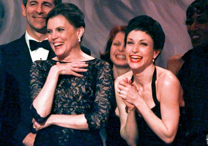 Ann Reinking (links) en actrice Bebe Neuwirth lachen samen op het podium terwijl ze een prijs in ontvangst nemen.