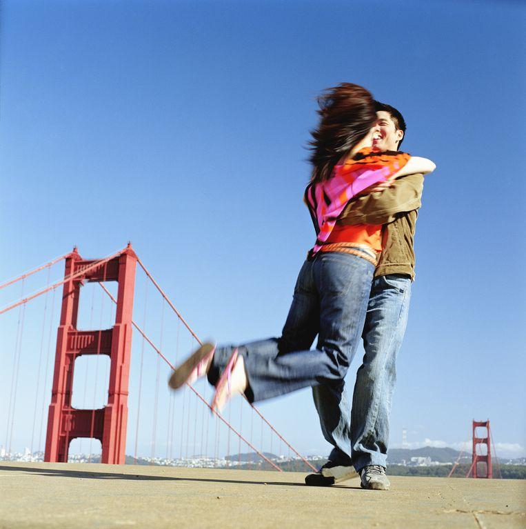 Stelletje springt in elkaars armen voor de Golden Gate Bridge. Beeld Getty Images