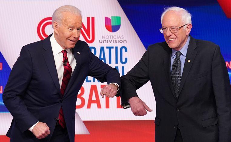 Joe Biden (links) en Bernie Sanders geven elkaar een elleboog in plaats van een hand, vanwege de corona-richtlijnen. Beeld REUTERS