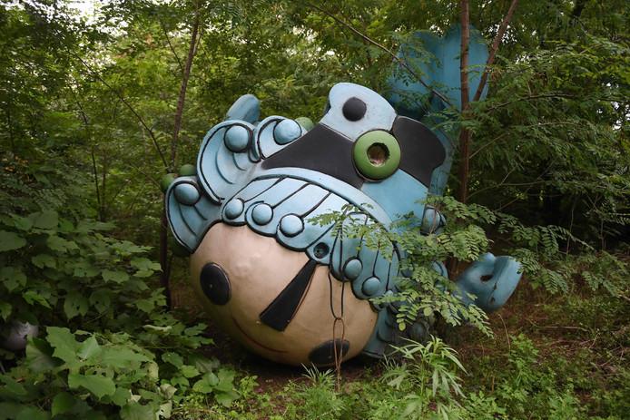Nog een mascotte, Beibei, ligt verlaten tussen de bomen, achter een verlaten, nooit afgemaakt shoppingcenter in Beijing.