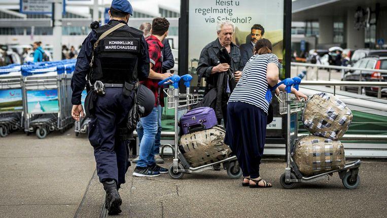 Leden van de Marechaussee controleren voor de ingang van vertrekhal 2 op Schiphol. Beeld anp