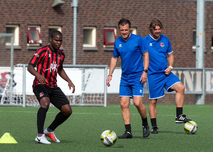 Jan Oosterhuis (midden) bekijkt de verrichtingen van DVC'26-speler Gideon Geertruida.