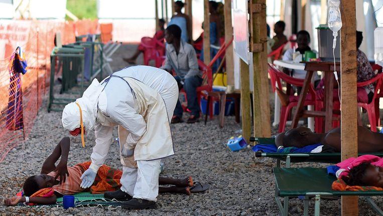 Een verpleegkundige controleert een ebola-patiënt in Sierra Leone. Beeld anp