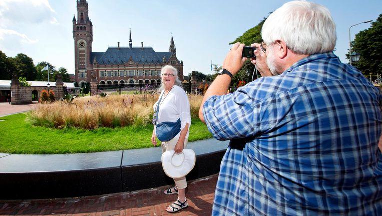 Een toerist wordt gefotografeerd voor het Vredespaleis in Den Haag Beeld anp