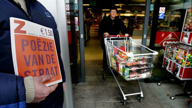Een dakloze verkoopt de Z!-krant bij een supermarkt. Beeld anp