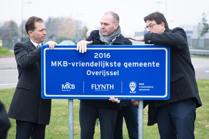 Gedeputeerde Eddy van Hijum, ondernemer Erik Huzen en wethouder Bert Tijhof (v.l.n.r.) onthullen een bord