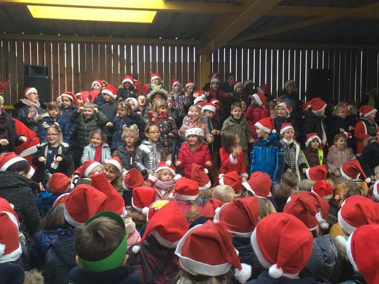 De kinderen zongen op de speelplaats kerstliedjes.