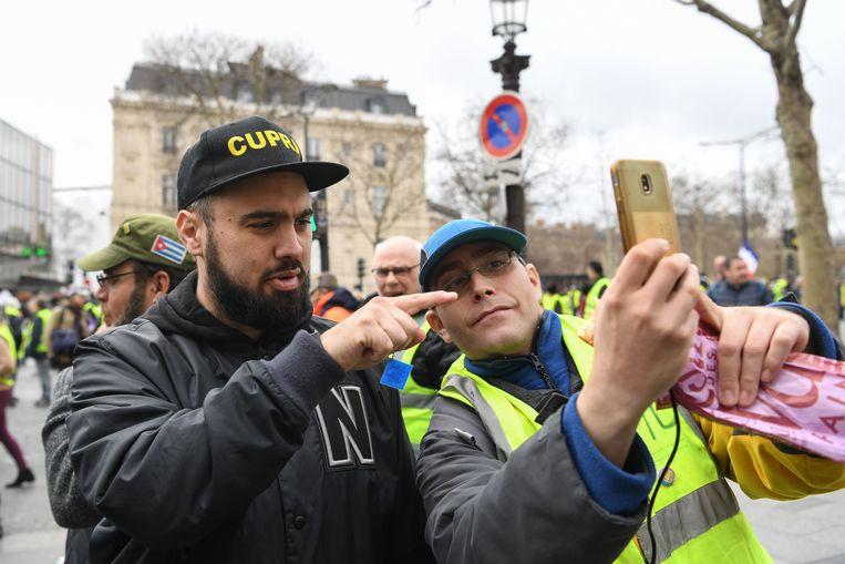 Een betoger neemt een selfie met Eric Drouet (links).