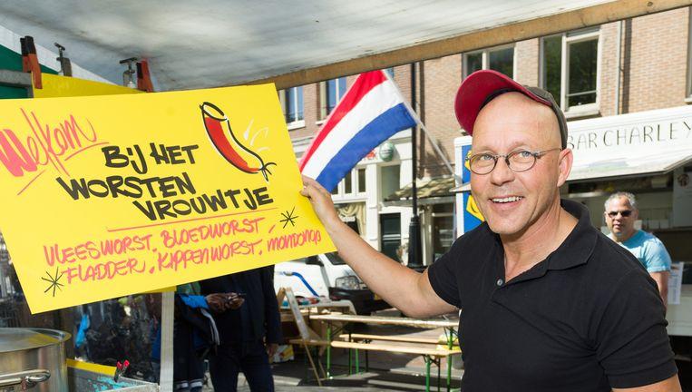 Henry van der Horst met een door hem beschreven bord op de Dappermarkt in Amsterdam. Beeld Ivo van der Bent