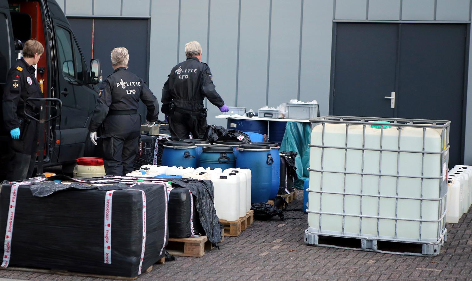 Specialisten van de politie druk doende om de chemicaliën en andere spullen af te voeren van een XTC-lab.