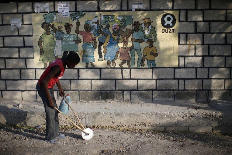 Een jongetje loopt langs een Oxfamposter in Port-au-Prince.