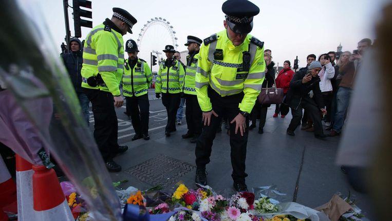 Britse politieagenten leggen bloemen op de Westminster Bridge voor de slachtoffers van de aanslag van afgelopen woensdag. Beeld afp