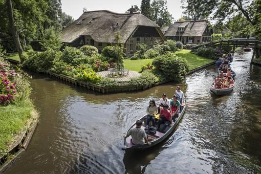 Toeristen die met fluisterbootjes door Giethoorn varen.