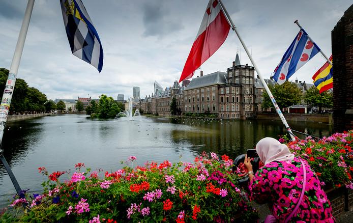 Toeristen genieten bij de Hofvijver van het uitzicht op het historische Binnenhof.