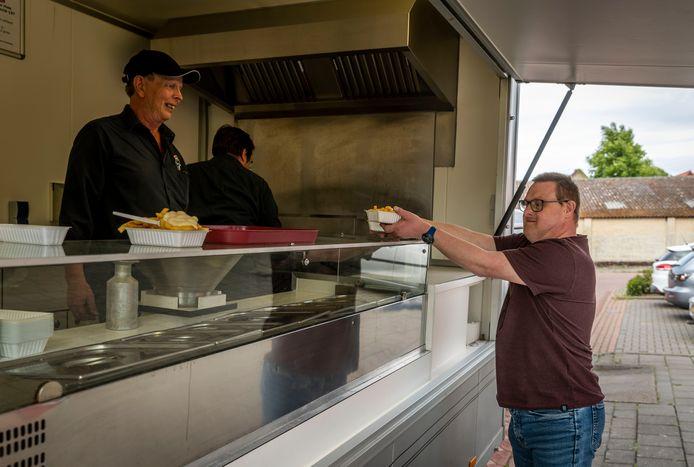 Cliënten van d'n Boegent in Reusel krijgen friet van de frietkar van Mark van Buul.
