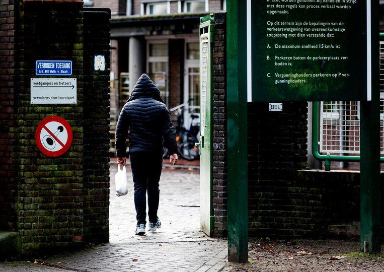 Een asielzoeker gaat de poort van het azc in Weert binnen. Beeld Robin van Lonkhuijsen, ANP