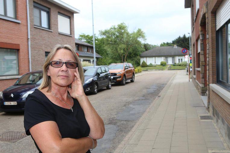 Bewoonster Conny Cauberghs in de doodlopende straat, met op de achtergrond de witte villa.