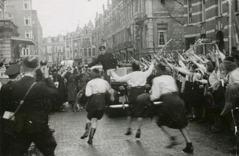 Mussert wordt in de Jan Willem Brouwerstraat uitbundig onthaald door meisjes van de Jeugdstorm na door Hitler te zijn erkent als 'Leider van het Nederlandse volk', 13 december 1942. Beeld Foto: NIOD / N.V. Polygoon, M.E.F. Sagers
