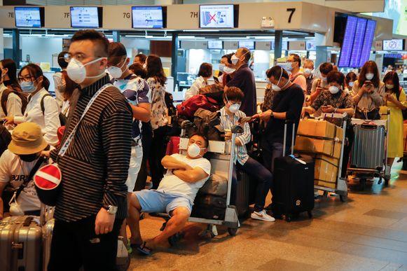 Wachtende toeristen dragen mondmaskers op de Don Mueang-luchthaven in Bangkok. Ook in Thailand zit de schrik er goed in door de uitbraak van het coronavirus.