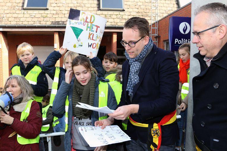 De leerlingen overhandigen hun petitie aan burgemeester Stijn Raeymaekers.