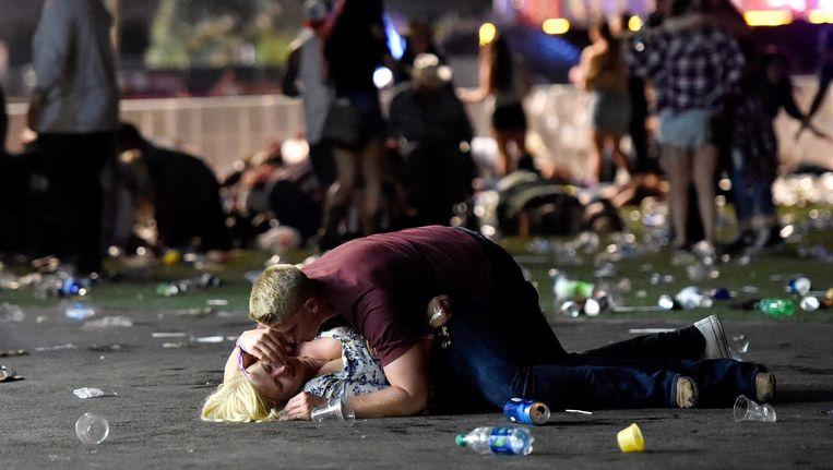 Een jongen ontfermt zich over een slachtoffer van de schietpartij in Las Vegas, terwijl om hen heen bezoekers van het festival op de vlucht slaan. Beeld AFP