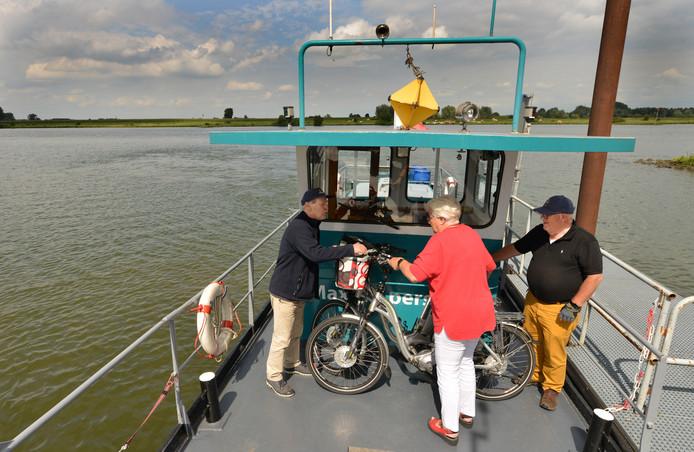 Joop Kloof en Eric van Grieken helpen Willemien Pels met haar fiets op het Liniepontje bij Culemborg.