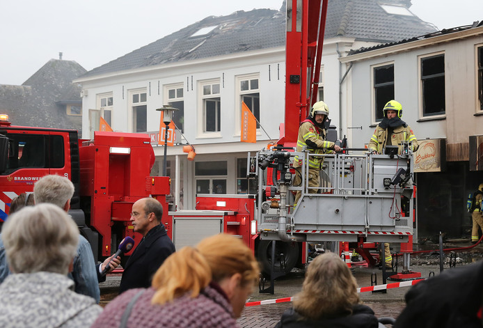 Burgemeester Alex van Hedel (zwarte jas) staat de pers te woord op het geschonden Brummense Marktplein. ,,Brummen is door een brand wederom diep in het hart getroffen.''