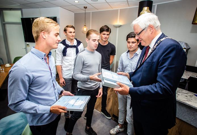 De helden krijgen een certificaat van de burgemeester. Thomas staat rechts naast hem.