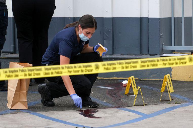 Een inspecteur van de politie verzamelt bewijsmateriaal bij het tankstation in Noord-Hollywood waar de schutter een vrouw vermoordde en een bediende zwaar verwondde.