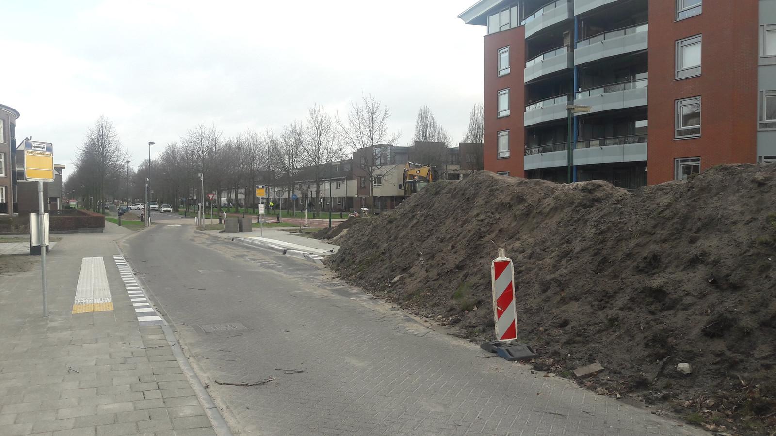 Een berg zand langs de bussluis.