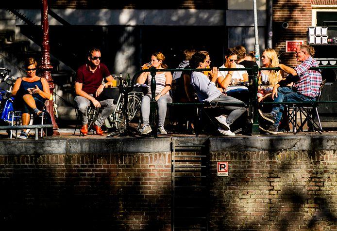 Mensen genieten van zomers weer in Amsterdam.