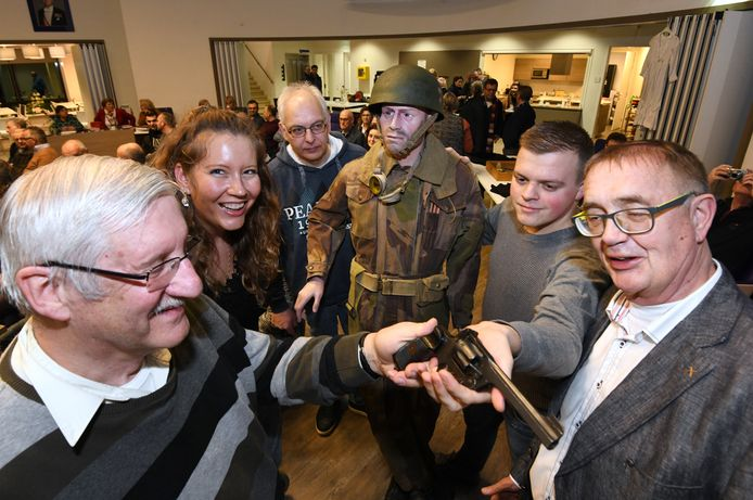 Sem Arends (tweede van rechts) toont een revolver tijdens zijn lezing over de Tweede Wereldoorlog.