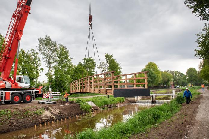 Na enige vertraging -de brug bleek te zwaar voor de aanwezige kraan- ligt de nieuwe fietsbrug over het Peelkanaal.