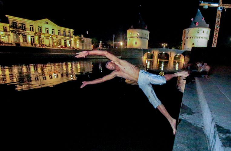 Een van de wildzwemmers, terwijl hij in de Leie duikt.